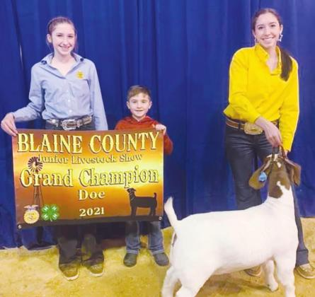 Reese Coleman (left) holds a sign for Riley Coleman (right) as she poses with her Grand Champion Doe (Photo provided by Watonga FFA)